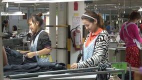 Fábrica do vestuário de matéria têxtil: Calças de brim terminadas tipo dos trabalhadores novos na fábrica filme