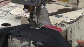 Fábrica do vestuário de matéria têxtil: Feche acima da parte da tela do vestuário e da máquina de costura vídeos de arquivo