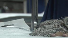 Fábrica do vestuário de matéria têxtil: Feche acima do corte da luva e da serra de fita de metal video estoque