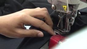 Fábrica do vestuário de matéria têxtil: A mão do CU coloca a tela preta na máquina de costura filme