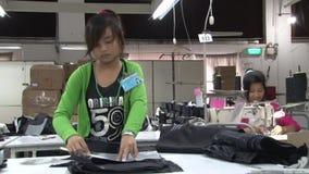 Fábrica do vestuário de matéria têxtil: O trabalhador de vestuário aplica o teste padrão à tela filme