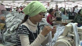 Fábrica do vestuário de matéria têxtil: O trabalhador de vestuário prepara e costura seções da tela video estoque