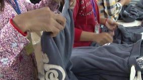 Fábrica do vestuário de matéria têxtil: Os tipos do trabalhador terminaram camisetas vídeos de arquivo