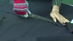 Fábrica do vestuário: O trabalhador corta a tela com grandes tesouras vídeos de arquivo