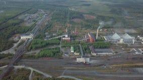 Fábrica e construções industriais perto da estrada e da estrada de ferro Silhueta do homem de negócio Cowering filme