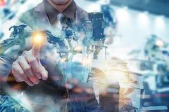 Fábrica esperta de Iot, indústria 4 0 conceitos da tecnologia, mão do ponto do coordenador com o robô no fundo da fábrica da auto fotografia de stock