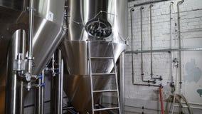 Fábrica moderna de la cervecería Fila de los tanques en cervecería Fermentación en los tanques de una cervecería con la cerveza p metrajes