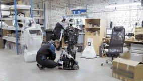 Fábrica para la producción de robots El ingeniero examina el robot Crea un nuevo robot en el laboratorio Robot de las reparacione almacen de video