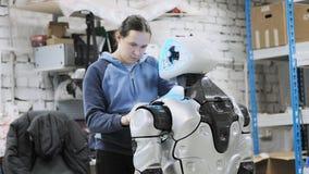 Fábrica para a produção de robôs O cientista reflete no dispositivo do robô Ajusta-se - acima e faz-se ajustes filme