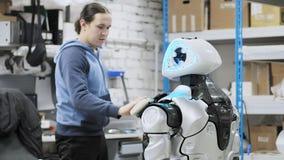 Fábrica para a produção de robôs O cientista reflete no dispositivo do robô Ajusta-se - acima e faz-se ajustes video estoque