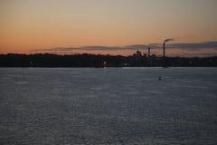 Fábricas con las chimeneas del smokey por el río en la puesta del sol fotos de archivo libres de regalías