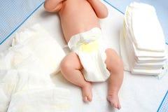 Füße des neugeborenen Babys auf ändernder Tabelle mit Windeln Nettes kleines Mädchen oder Junge zwei Wochen alt Trockener und ges stockfoto