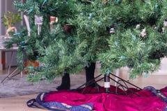 Füße hinter einem künstlichen Weihnachtsbaum lizenzfreie stockfotos
