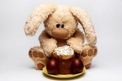 Füllte weiches Kaninchen mit Ostern-Kuchen an und malte Eier auf einem weißen Hintergrund lizenzfreie stockfotografie