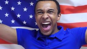 Fã americano Celebrates que guarda a bandeira dos EUA no movimento lento foto de stock