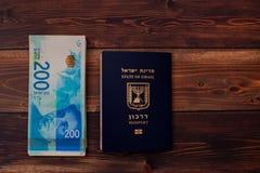 Fã de dois cem contas israelitas do shekel junto com o passaporte israelita Imagens de Stock Royalty Free