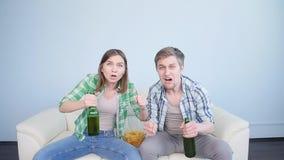 Fã de esportes entusiasmado dos pares que olha a tevê em um sofá na sala de visitas vídeos de arquivo