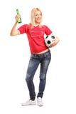 Fã de esportes fêmea que guarda a cerveja e um futebol Fotografia de Stock