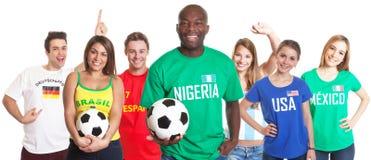 Fã de futebol de riso de Nigéria com bola e outros fãs Imagens de Stock Royalty Free