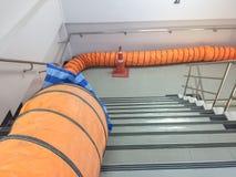 Fã do tubo com espaço limitado, fãs de ventilação portáteis e exaustores na escada na fábrica fotografia de stock