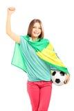 Fã fêmea feliz com a bandeira brasileira que guardara uma bola de futebol imagens de stock