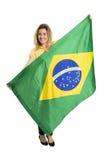 Fã fêmea feliz com a bandeira brasileira que guardara uma bola de futebol imagem de stock royalty free
