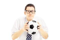 Fã masculino com o laço que guarda uma bola de futebol e que espera a contagem imagem de stock