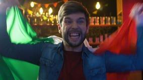 Fã masculino entusiasmado que acena a bandeira italiana, vitória nacional de júbilo da equipe de esportes filme