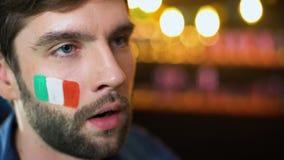 Fã masculino farpado nervoso com a bandeira italiana no mordente que faz o facepalm, perda da equipe filme