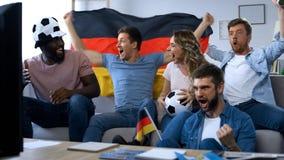 Fãs alemães entusiasmados que cheering para a equipe de futebol favorita, comemorando a vitória fotos de stock