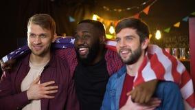 Fãs americanos patrióticos que cheering para a equipe, o hino do canto e a bandeira de ondulação no bar filme