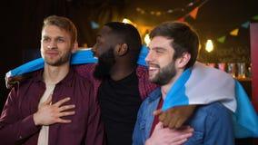 Fãs argentinos alegres que cheering para a equipe de futebol, hino do canto, bandeira de ondulação vídeos de arquivo
