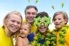 Fãs de futebol brasileiros da família que comemoram. Imagens de Stock
