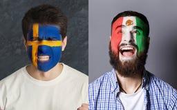 Fãs de futebol emocionais com as bandeiras pintadas nas caras Imagem de Stock