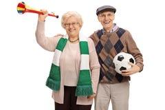 Fãs de futebol idosos alegres com uma trombeta e um futebol fotografia de stock royalty free
