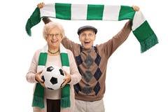 Fãs de futebol idosos extáticos com um futebol e um lenço Fotos de Stock
