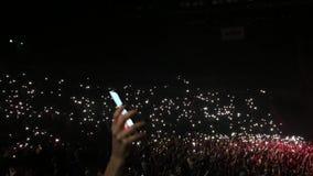 Fãs irreconhecíveis que guardam lanternas elétricas nos seus mãos em face da fase Atmosfera do concerto concert Cheering filme