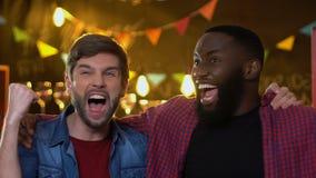Fãs masculinos multi-étnicos alegres que mostram sim o gesto, comemorando o objetivo da equipe nacional video estoque