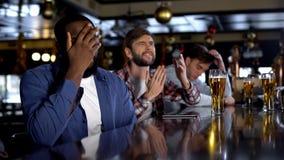 Fãs multi-étnicos que olham o campeonato no bar, desagradado com jogo perdedor imagens de stock royalty free