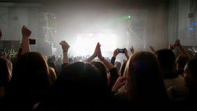 Fãs no concerto vivo, multidão de povos iluminados pelas luzes coloridas, aplaudindo com mãos acima filme