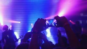 Fãs que acenam sua gravação das mãos video e tomada de imagens com os telefones espertos no concerto da música Multidão dos povos foto de stock