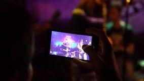 Fãs que cheering na audiência que acena seus mãos e telefones celulares da posse com indicações digitais a multidão em um concert video estoque