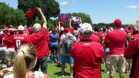 Fãs vermelhos Cheering de Shirted na reunião video estoque