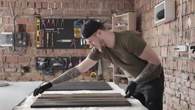 Fähigkeit bärtige craftman Funktionsstellung am Tisch in der Garage Ein Mann arbeitet in einer Werkstatt Das Brett mit den Werkze stock video footage