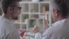 Fähigkeit zwei erfuhr männliche Doktoren, die den Röntgenstrahl der Lungen auf der Tablette überprüfen und besprach sich Konzept  stock video