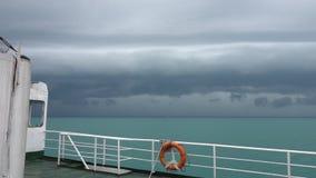 Fähre mit orange Lebensbojenringsegel im schlechten Wetter mit Gewitterwolken Sicherheit auf Sees-Konzept stock video footage