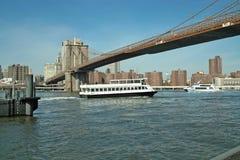 Fähre unter der Brooklyn-Brücke, New York, USA Stockfotos