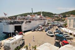 Fähre verankert im Pier und Leute und Autos, die an Land in Korcula, Kroatien warten lizenzfreies stockfoto