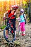Fährt Radfahrenfamilie rad Tragende Radfahrenfahrräder des Sturzhelms der Mutter und der Tochter Lizenzfreie Stockfotos