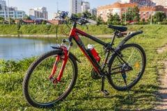 Fährt Sport auf ein grünes Gras nahe einem Stadtsee rad lizenzfreies stockfoto